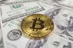 Gold Bitcoin on hundred dollars bills. Close-up, macro shot. royalty free stock photography