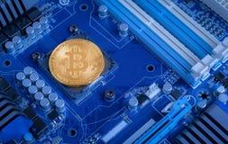 Gold-bitcoin Maschinenantrieb auf blauem Motherboard stockbilder