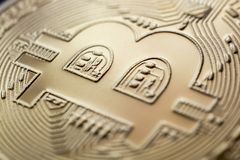 Gold bitcoin monet coin currency closeup. Bitcoin currency DOF on blue glass background. Gold metal curency symbol macro photo closeup royalty free stock photos