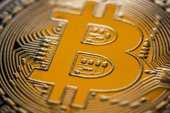 Gold Bitcoin monet coin on yellow light. Bitcoin currency DOF on blue glass background. Gold metal curency symbol macro photo closeup royalty free stock images