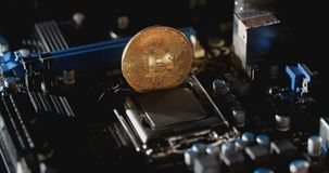 Gold bitcoin with motherboard rotates on the table. New crypto currency, bitcoin and computer fee finance. Gold bitcoin with motherboard. New crypto currency stock footage