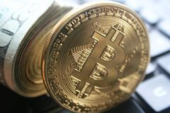 Gold Bitcoin With Roll Of Twenties On Computer Keyboard High Quality. Stock Photo Stock Image