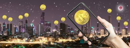 Gold bitcoin on screen smart phone with Building in Bangkok. At night time. Concept electronic money for future stock image