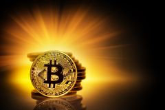 Gold bitcoin and a stack of coins in yellow rays. The concept of developing a new virtual currency. Toning Stock Photo