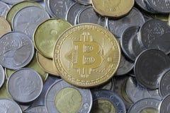 Bitcoin on Money. A gold Bitcoin Token on Canadian Cash stock photography