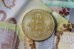 Gold Bitcoin Token on Cash. A gold Bitcoin Token on Canadian Cash Royalty Free Stock Photos