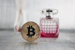 Gold-bitcoin und -parfüm stockfoto