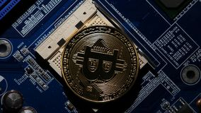 Gold Bitcoin virtual currency on a motherboard instead cpu. new metal cryptocurrency bitcoin on the circuit. Hand sets Silver Bitcoin virtual currency on a stock video