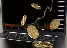 Gold Bitcoin virtual money falling on laptop keyboard stock photography