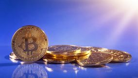 Gold bitcoins. On a blue background Stock Images