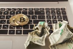 Gold bitcoins and crumpled dollars on laptop Stock Photography