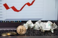 Gold bitcoins and crumpled dollars on laptop Stock Photos
