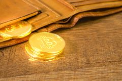 Gold bitcoins Crypto currency in brown leather wallet on wooden table royalty free stock image