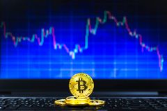 Gold bitcoins on key board and BTC trading chart in background, Financial concept. Gold bitcoins on key board and BTC trading chart in background, Financial Royalty Free Stock Photography