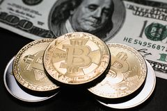 Bitcoin. Gold Bitcoins on a one hundred dollar bill close up. Gold Bitcoins on a one hundred dollar bill close up Stock Image