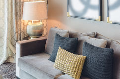 Gold and black color pillows on grey sofa Royalty Free Stock Photography