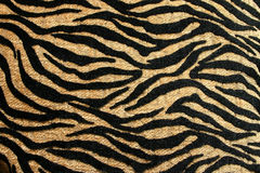 Gold and Black Tiger Design with Rich Texture. A close up of a gold and black tiger design print with varying texture that is on a pillow. Great for a background royalty free stock image