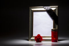 Gold, blank mourning frame with candle and carnation royalty free stock photo