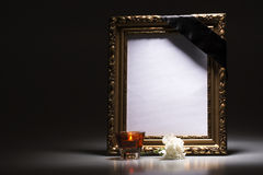 Gold, blank mourning frame with candle and carnation Royalty Free Stock Images