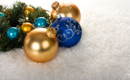 Gold and blue christmas balls with branch. Fir tree on snow Stock Images