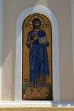 Gold and blue mosaic of bearded saint on Greek Island. Gold and blue mosaic of saint with beard set in niche of church wall on Greek Island of Psirimos royalty free stock photography