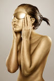 Gold bodypainted girl. Topless gold bodypainting on a brunette girl Stock Photography