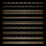 Gold borders. Set of vintage gold wavy borders, ornamental dividers on black Royalty Free Stock Photography