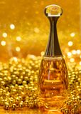 Gold bottle parfume close-up dior bokeh background glitter glass reflection shine garland. Gold bottle parfume close-up dior bokeh background glitter macro light royalty free stock photo