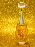 Gold bottle parfume close-up dior bokeh background. Glitter macro light beautiful abstract blur texture royalty free stock photography
