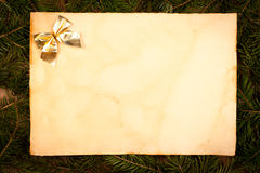 Gold bow on aged paper sheet Stock Images