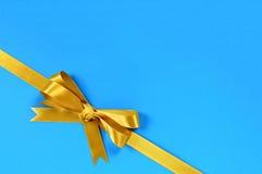 Gold bow gift ribbon corner diagonal blue background Stock Photos