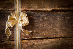 Gold bow on a grunge wood background. Festive ornamental gold ribbon and bow on a grunge rustic wood background with copyspace for your Christmas, anniversary or Royalty Free Stock Image