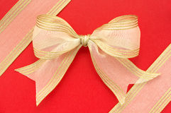 Gold bow on red background. Royalty Free Stock Photos