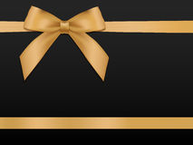 Gold Bow with ribbons. Shiny holiday gold satin ribbon on black Stock Photo