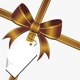 Gold bow with tag. Gold ornamental bow with white empty tag Royalty Free Stock Images
