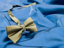 Gold bow tie against blue satin background Stock Images