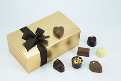 Gold box with assorted chocolates. Gold chocolate box with ribbon and assorted chocolates Royalty Free Stock Photos