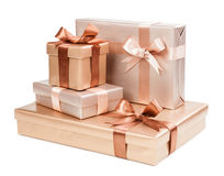 Gold box with gifts and brown bow Stock Photos