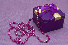 Gold box with purple bow and pearls Stock Photos