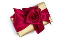 Seasonal gold box wrapped with a Red Ribbon. A gold box that has been gift wrapped with a red ribbon Stock Photo
