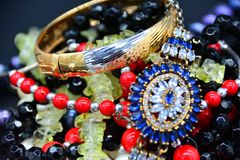Gold Bracelet And Pendant With Blue Stones, Coral Beads Against A Dark Background. Stock Photography