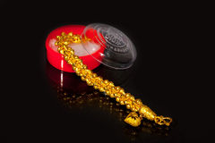 Gold bracelet. Isolated gold bracelet with package in black background Stock Image