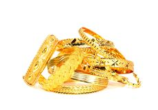 Gold bracelets on white stock photos