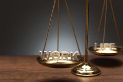Gold brass balance scale on wooden desk and gray backdrop stock image