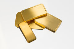 Gold bricks, white background, light reflections Royalty Free Stock Photo