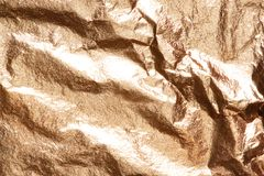 Gold bright shiny texture of a crumpled sheet. Gold bright shiny real texture of a crumpled sheet royalty free stock photos