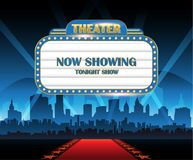 Gold brightly theater glowing retro cinema neon sign with city in background Stock Photos