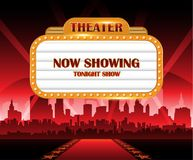 Gold brightly theater glowing retro cinema neon sign with city in background Royalty Free Stock Photos