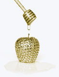Gold brilliant apple with drop of honey on dipper Stock Photos