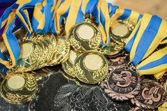 gold and bronze medals with yellow- blue ribbons on a silver tray, Champions awards, the third place prize for the winner, it is stock images